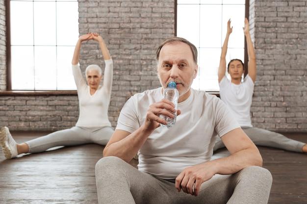 膝に手を置きながら水を飲むスポーツ服を着て疲れた男性