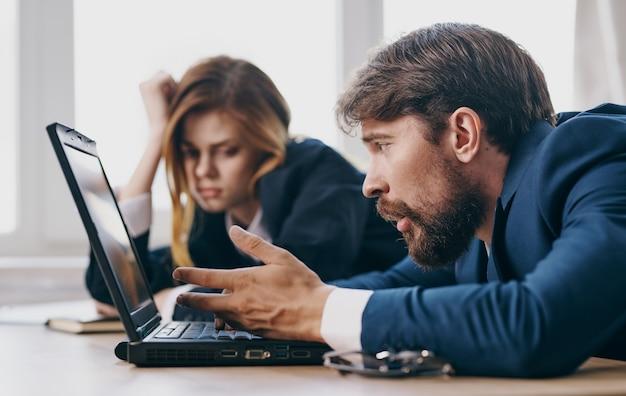 仕事のラップトップの専門家で仕事の同僚で疲れた男と女