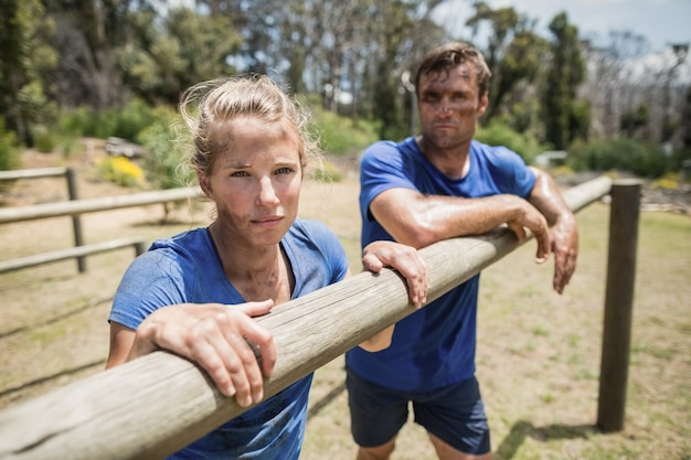 Усталые мужчина и женщина, опираясь на препятствие во время полосы препятствий в учебном лагере