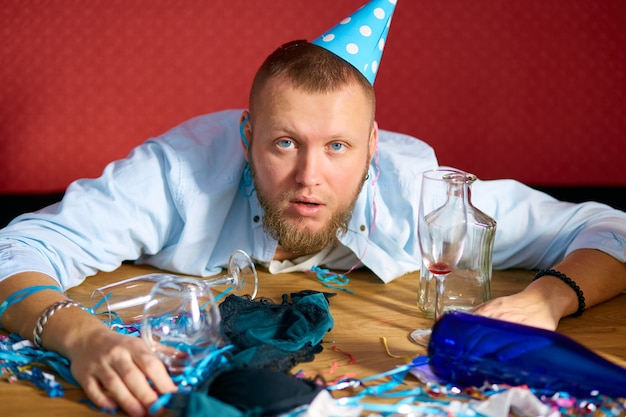 생일 파티 후 지저분한 방에 파란색 모자가있는 테이블에서 피곤한 남자, 집에서 파티 후 피곤한 남자