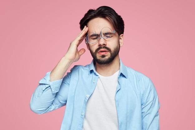 피곤한 남자는 눈을 감고 고통을 느끼면서 관자놀이에 손을 댄다.