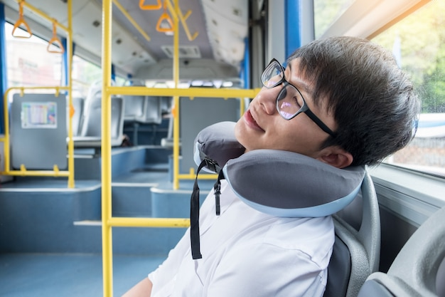 Tired man comfortably in bus and sleeping with cervical neck inflatable pillow, transport