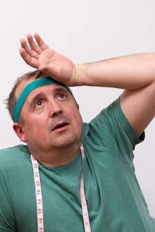 Tired man in a green bandana and a t-shirt with a measuring tape around his neck