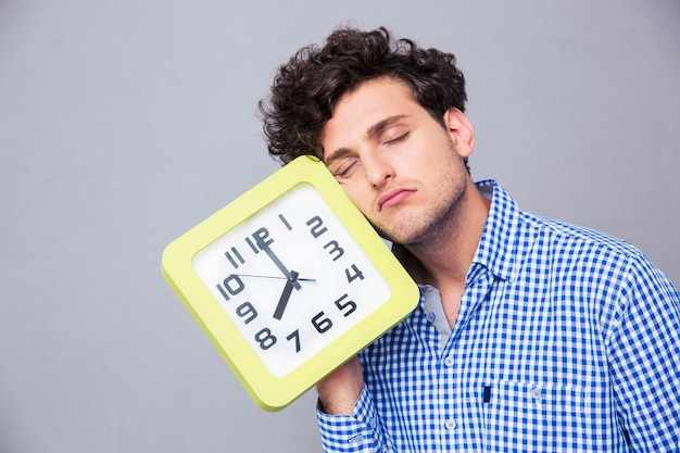 Tired man holding big clock