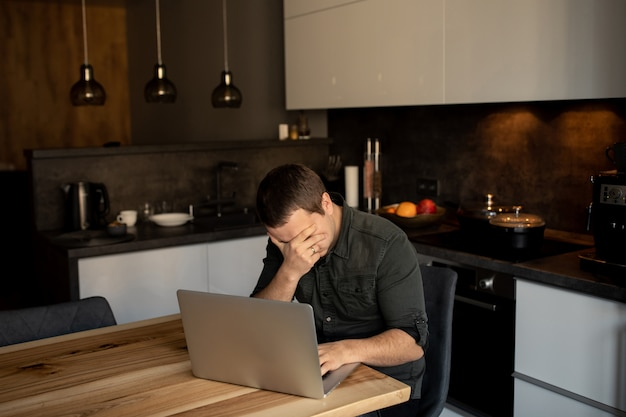 Tired man holds his head while working on a laptop indoors. online worker, freelancer in the home working place - kitchen room