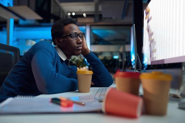 眼鏡をかけた疲れた男は、コンピューター、オフィスライフスタイルで働いています。デスクトップ、暗いインテリア、モダンな職場で男性