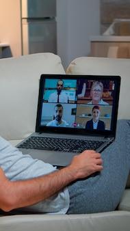 잠옷을 입은 피곤한 남자는 노트북 컴퓨터를 사용하여 팀원들과 온라인 비즈니스 화상 통화를 하는 동안 소파에 앉아 잠들었습니다. 회의 인터넷 웹 통신에 백인 남성