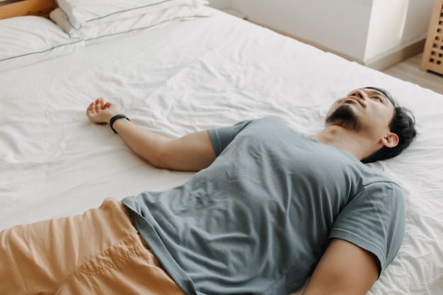 Tired man is lying on the bed as he out of energy