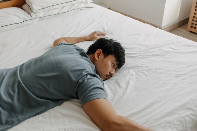 疲れた男がエネルギー不足でベッドに横たわっている