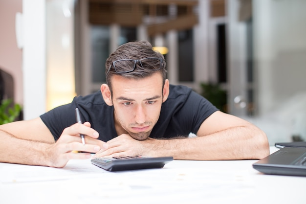 Tired man lying on desk with calculator