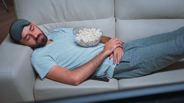 Tired man lying on sofa watching movie show