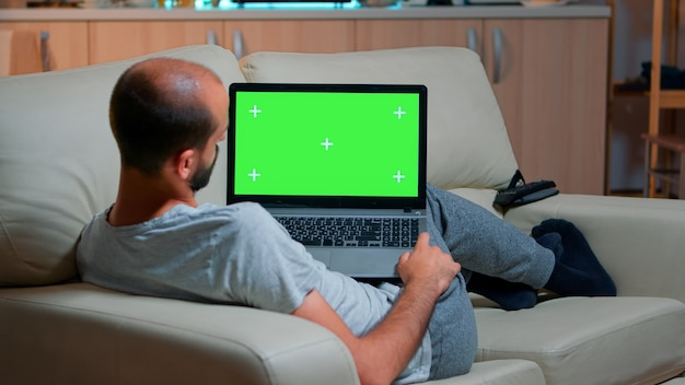 Tired man lying on sofa working on computer