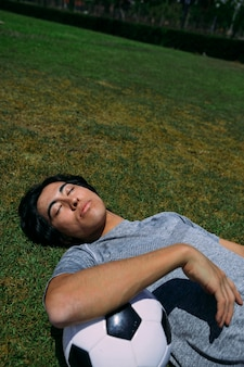 Tired man lying with eyes closed on grass with football