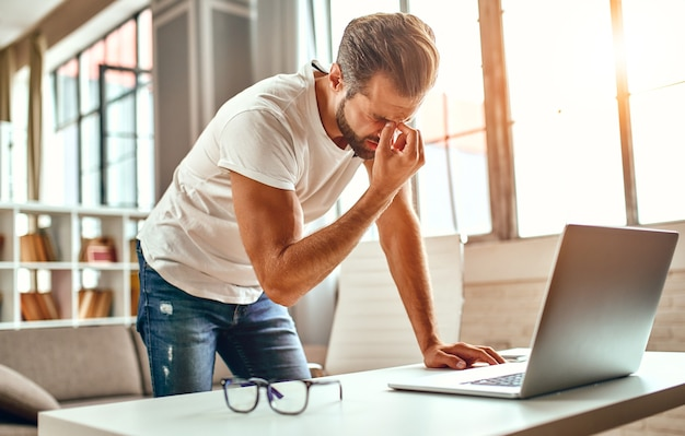 The tired man put his fingers on the bridge of his nose, a migraine attack. freelance, work from home. a man works at a laptop.