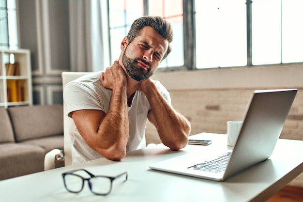 The tired man put his hands on his neck, in pain. freelance, work from home. a man works at a laptop.