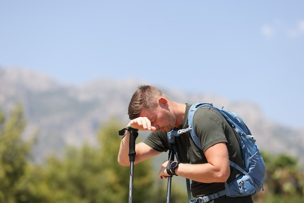 산에서 지팡이에 그의 머리를 넣어 피곤된 남자. 익스트림 여행 컨셉의 어려움