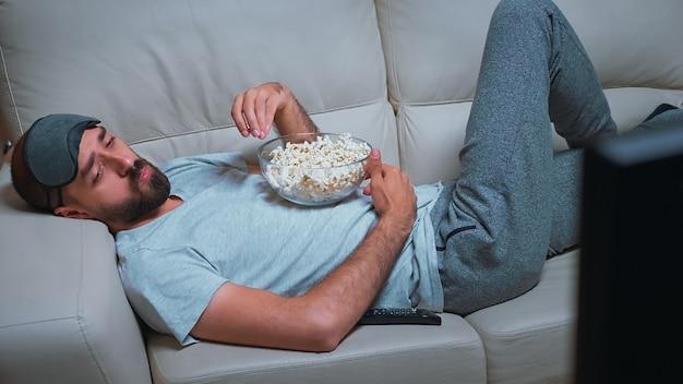 Усталый мужчина отдыхает на диване перед телевизором, ест попкорн во время просмотра фильма