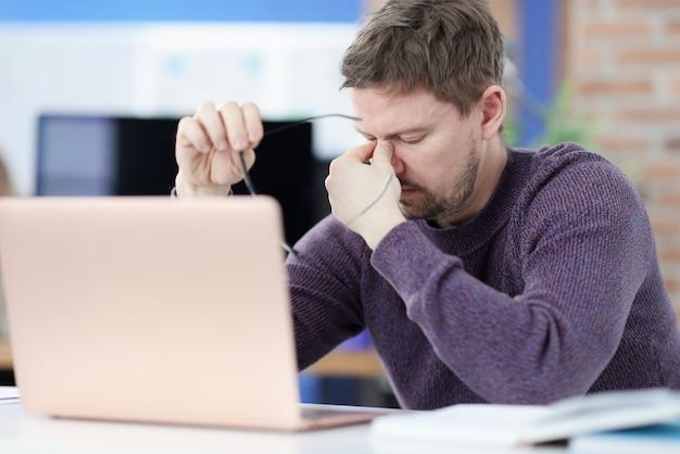Усталый мужчина сидит перед экраном ноутбука и держит в руках очки