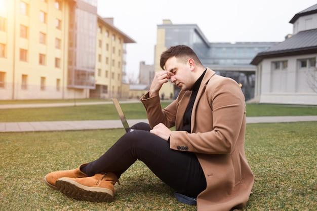 疲れた男は彼の手にラップトップを使って芝生の上に座っています。