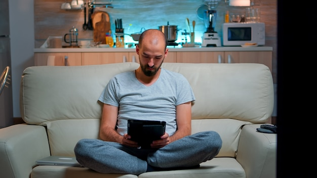 Tired man sitting alone on couch while browsing on internet using tablet computer with modern technology wireless. caucasian male in pajamas relaxing in front of televion late at night in kitchen