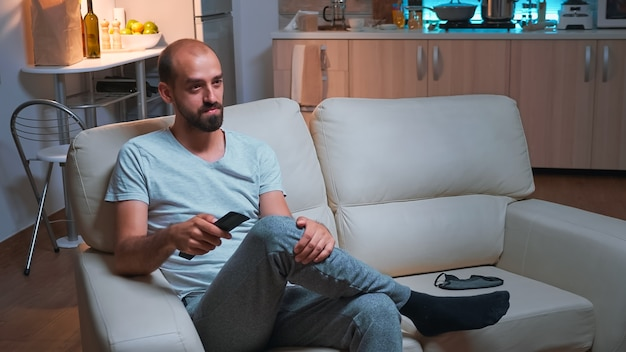 Tired man sitting in front of television watching entertainment movie series