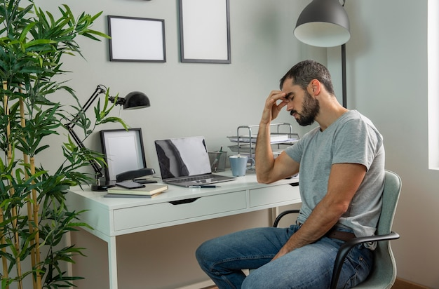 Tired man sitting at his home desk