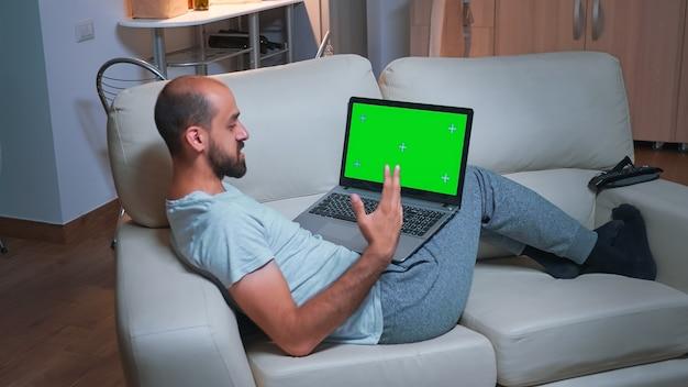 노트북 컴퓨터를 사용하여 마케팅 정보를 검색하는 동안 소파에 앉아 피곤한 남자