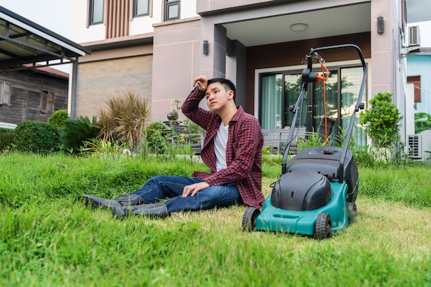家で草刈りのために芝刈り機で座っている疲れた男