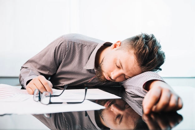 Uomo stanco che dorme nell'ufficio