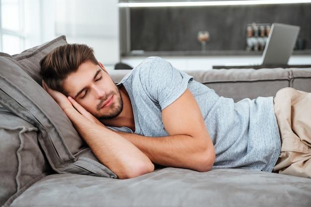 Усталый мужчина спит на диване. глаза закрыты.