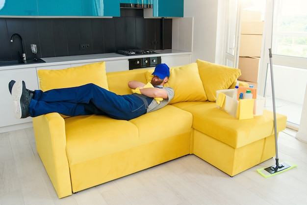 Tired man in special uniform sleeps on couch after cleaning cuisine.