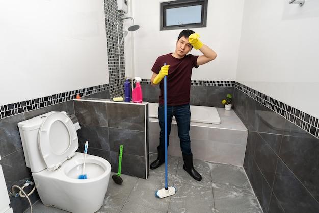 家のバスルームを掃除するのに疲れた男