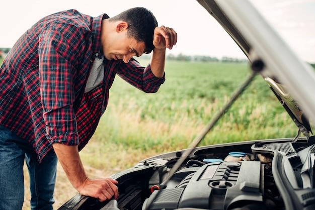 Tired man tries to repair a broken car