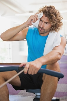 Tired man using resistance band in gym