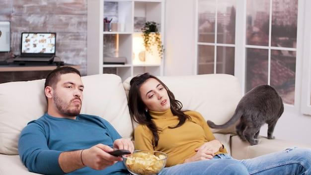 彼のガールフレンドが猫と遊んでいる間、ソファに座ってテレビのリモコンを使用している疲れた男。