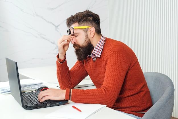 Усталый человек с ноутбуком на рабочем месте. бородатый мужчина перегружен в офисе. подчеркнул красивый деловой человек. чувствовать себя опустошенным. молодой человек, имеющий напряженное время работает на ноутбуке