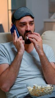 Усталый мужчина с маской для сна разговаривает по смартфону
