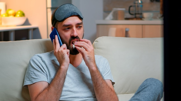 Tired man with sleep mask put talking on smartphone