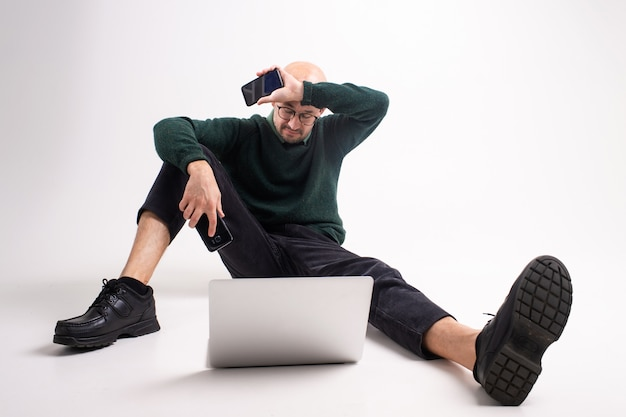 Tired man with two phones and laptop studio portrait
