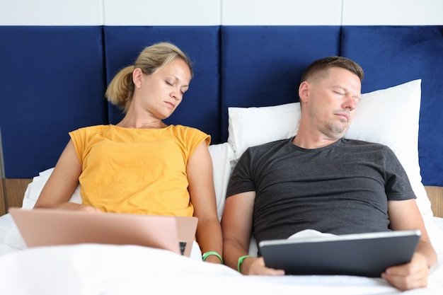Tired man and woman sleep in bed with laptops overtime teleworking concept