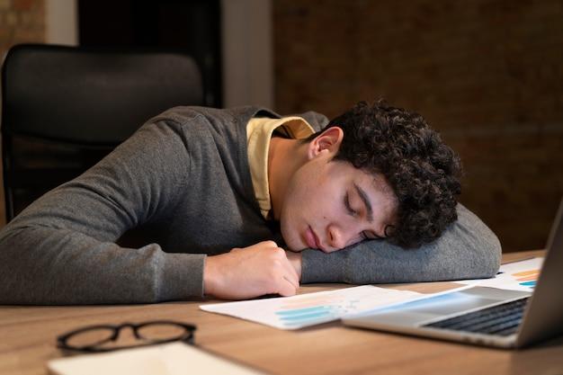 Усталый мужчина работает допоздна в офисе