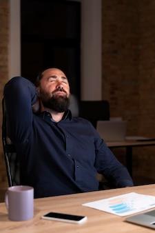 Uomo stanco che lavora fino a tardi per un progetto urgente