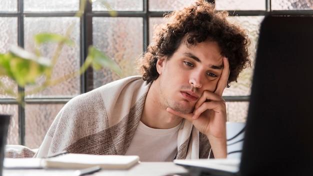 Усталый человек, работающий на ноутбуке