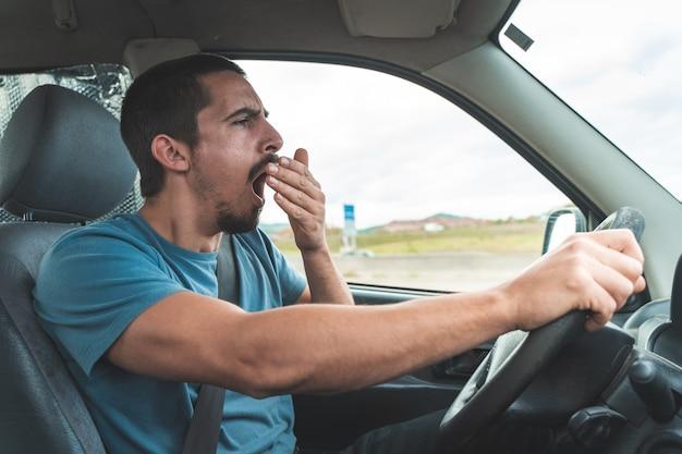 車を運転しながらあくびをする疲れた男