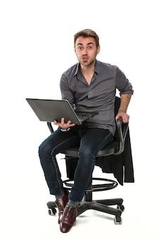 ノートパソコンが動作している椅子に座って疲れたマネージャー。それは前向きな感情を示しており、左手を椅子にかざし、右手をラップトップにかざしています。スタジオ、白い背景。