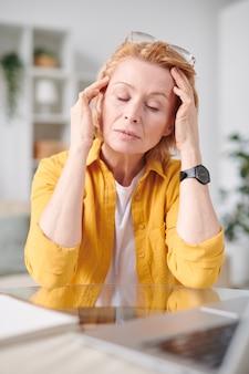 家庭環境の職場で頭痛に苦しんでいる間、頭に触れるカジュアルウェアで疲れた成熟した実業家
