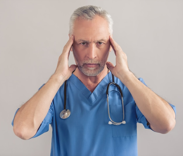 Tired mature doctor in blue medical wear