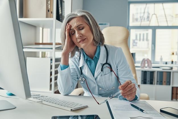 Усталая зрелая женщина-врач в белом лабораторном халате с закрытыми глазами сидит в своем офисе