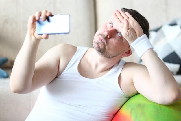 Утомленный зрелый человек после фитнеса дома