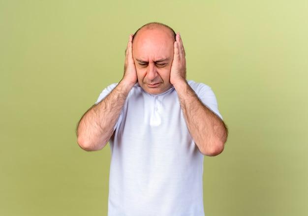 Uomo maturo stanco rannicchiava le orecchie con le mani isolate sulla parete verde oliva